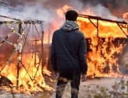 "A migrant looks at shacks burning during the dismantling of half of the ""Jungle"" migrant camp in the French northern port city of Calais, on February 29, 2016. Clashes broke out between French riot police and migrants on February 29 as bulldozers moved into the grim shantytown on the edge of Calais known as the ""Jungle"" to start destroying hundreds of makeshift shelters. AFP PHOTO / PHILIPPE HUGUENPHILIPPE HUGUEN/AFP/Getty Images"