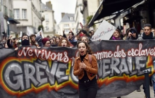 TOPSHOT - A young woman shouts slogans in front of a banner as thousands of people demonstrate on March 9, 2016 in Nantes, western France, as part a nationwide day of protest against proposed labour reforms. France faced a wave of protests against deeply unpopular labour reforms that have divided an already-fractured Socialist government and raised hackles in a country accustomed to iron-clad job security. / AFP PHOTO / LOIC VENANCE