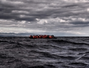 TOPSHOTS Refugees and migrants sail towards the Greek island of Lesbos on October 24, 2015 as they cross the Aegean sea from Turkey.  At least three migrants -- two children and a woman -- drowned when their boat sank off the Greek island of Lesbos, the coastguard said, the latest fatalities in Europe's refugee crisis. Around a dozen others, mostly Afghans, are still missing after the rickety vessel, carrying 60 people, went down at dawn as it made the perilous crossing from Turkey, according to the Greek coastguard. AFP PHOTO / ARIS MESSINIS